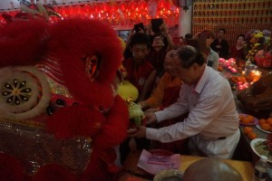 古晋佛教居士林在大年初一也邀请舞狮队前来贺节。图为蔡明田林长及释学闻法师从舞狮口中接过彩青是影。